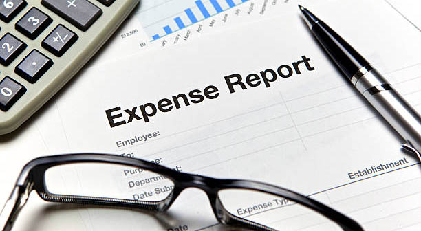 Close up of an expense form with calculator and pen.